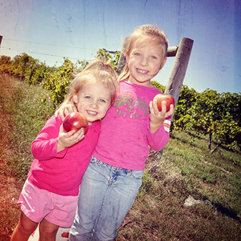two girls holding apples